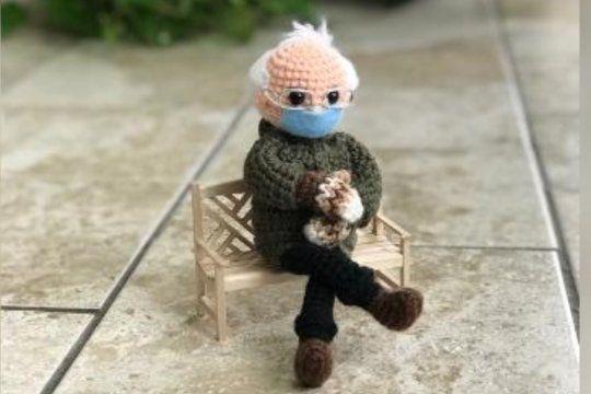 El muñeco de lana tejido al crochet que representa el meme de Bernie Sanders en la asunción de Biden sentado y con mitones marrones