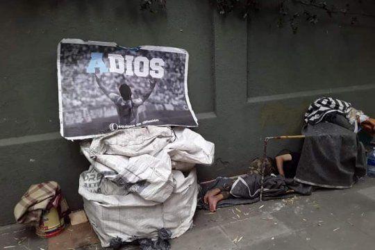 Los pies desnudos del hombre en situación de calle y el afiche de Maradona en su muro.