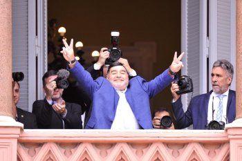 Diego Armando Maradona saluda desde el balcón de la Casa Rosada.