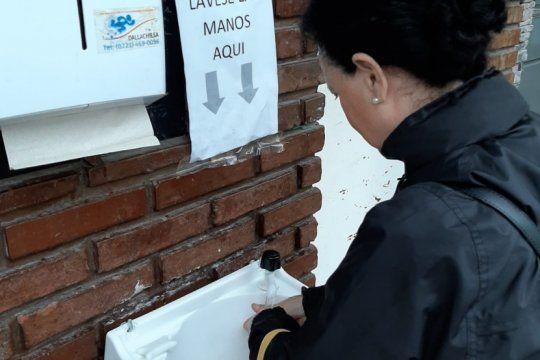 a falta de alcohol en gel, un supermercado platense instalo una bacha con agua y jabon en la entrada