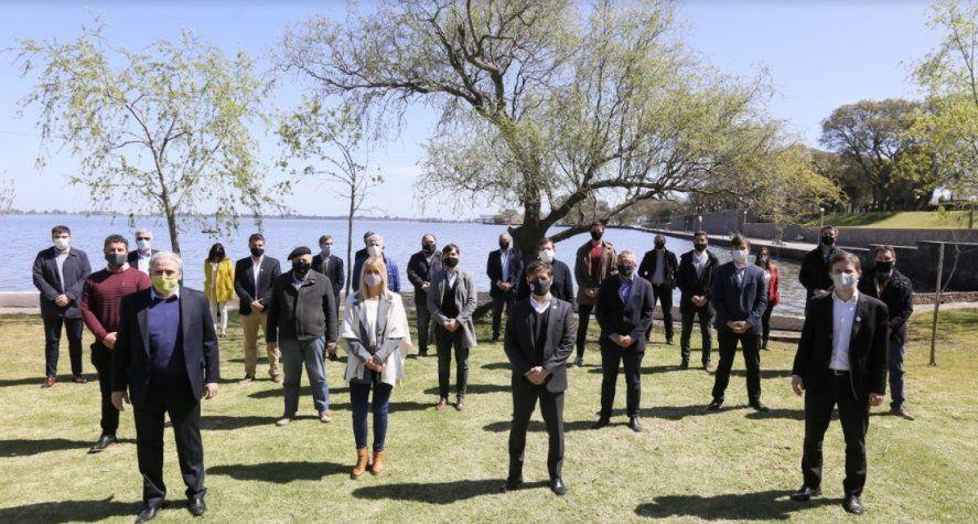 Kicillof junto a una docena de intendentes, junto a la laguna de Chascomús. Anunció que habrá temporada de verano.