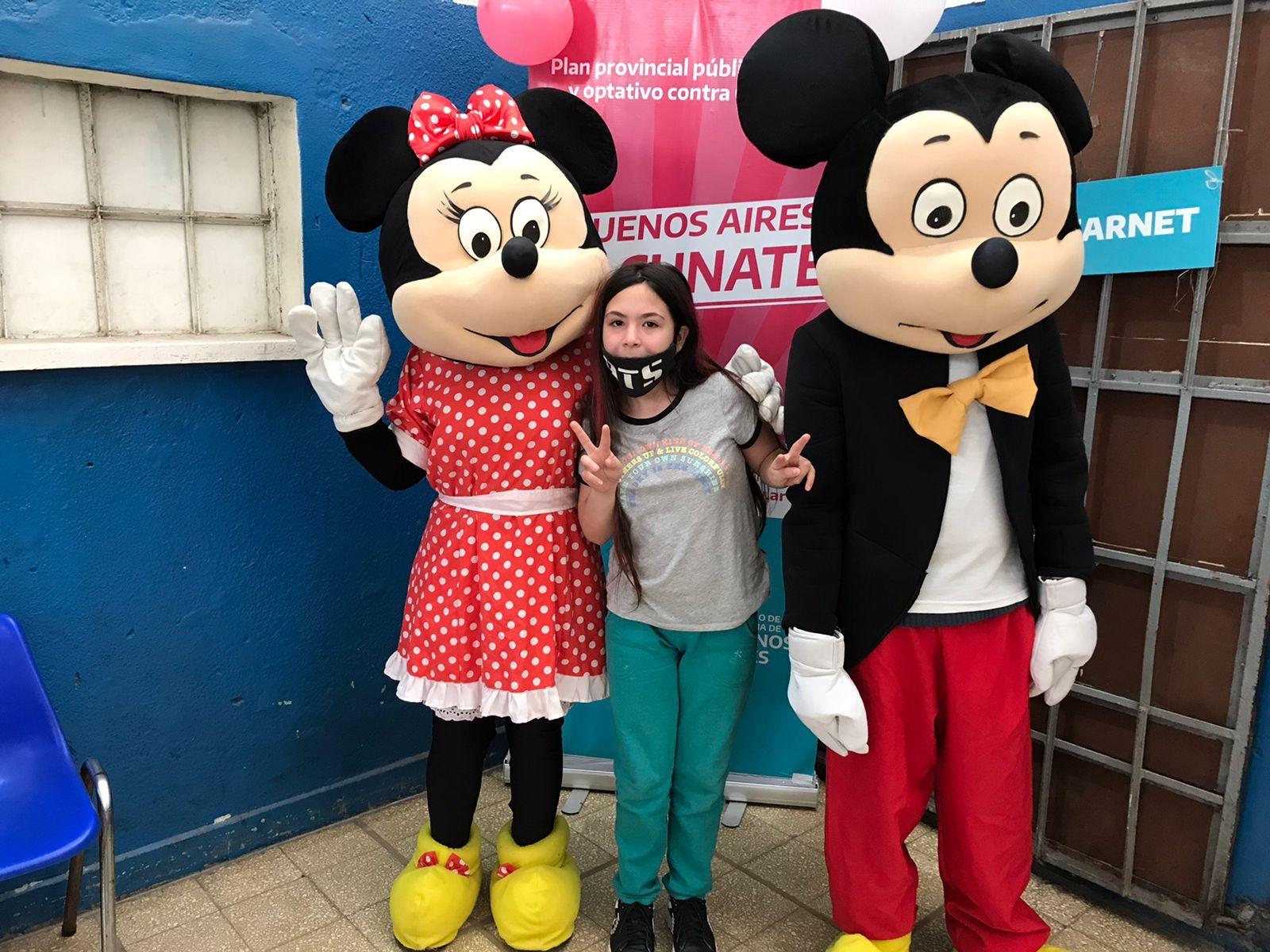 Mickey Mouse junto a otra persona diusfrazada de Minie y la niña que fue inminizada