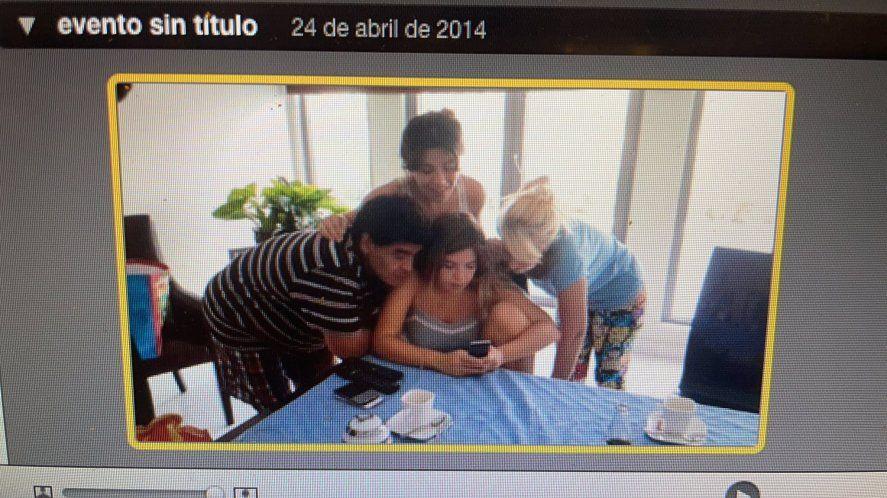 Diego, Gianinna, Dalma y Claudia Villafañe revisando algún contenido de un celular en 2014